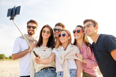friendship, leisure and people concept - group of happy friends taking picture by smartphone on selfie stick on beach in summer
