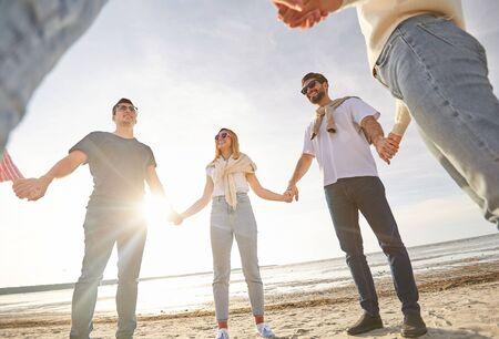 friendship, leisure and people concept - group of happy friends holding hands on beach in summer