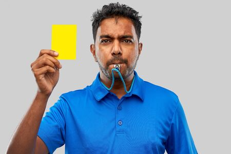sport, caution, game and football concept - indian referee whistling and showing yellow card Фото со стока