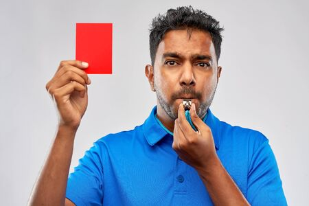 sport, caution, game and football concept - indian referee whistling and showing red penalty card