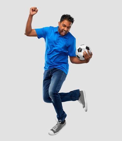 sport, leisure games and people concept - happy indian man or football fan with soccer ball jumping over grey background