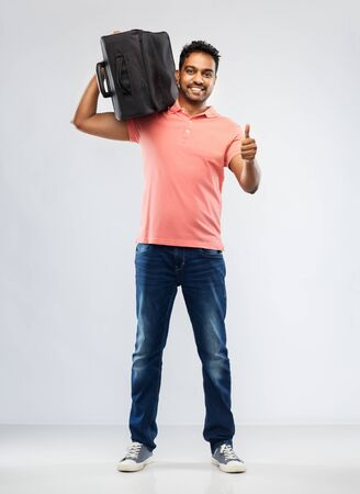 family, tourism and vacation concept - smiling indian man in polo shirt holding travel bag on shoulder over grey background Stock Photo