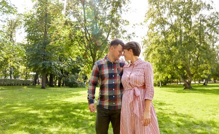 people and relationships concept - happy couple in summer park