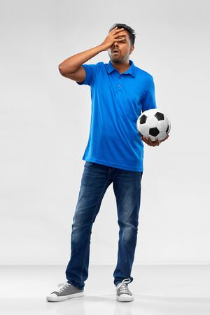 sport, leisure games and failure concept - disappointed indian man or football fan with soccer ball over grey background