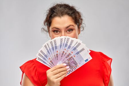 people and finances concept - happy woman in red dress hiding her face behind euro money banknotes over grey background