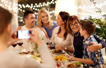 familia cenando y tomando selfie Foto de archivo