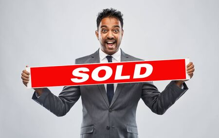 happy indian male realtor with red sold banner
