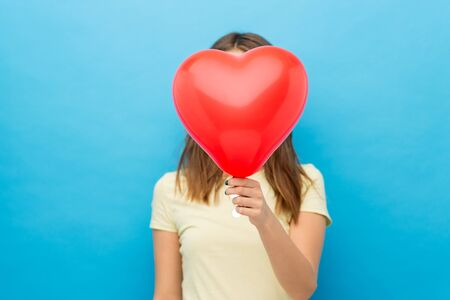 woman covering face with heart-shaped balloon Stock fotó - 131259445