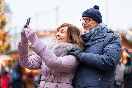 senior couple taking selfie at christmas market