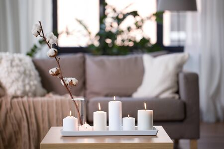 burning white candles on table at cozy home