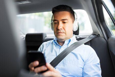 pasażer ze słuchawkami korzystający ze smartfona w samochodzie Zdjęcie Seryjne