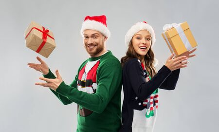 happy couple in christmas sweaters with gifts Stockfoto - 131460498