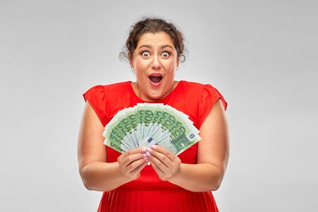 shocked woman holding hundreds of money banknotes