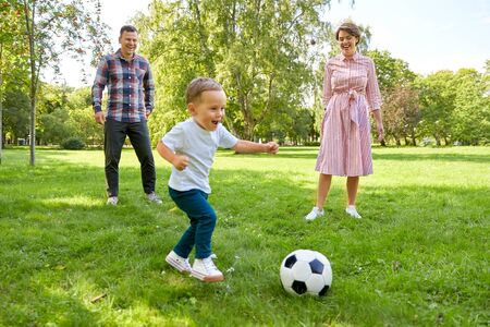 happy family playing soccer at summer park