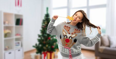 christmas, people and holidays concept - happy young woman wearing jumper with reindeer pattern and biting gingerbread party accessory at ugly sweater party over home room background