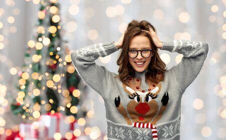 wintervakantie, feest en mensenconcept - gelukkige jonge vrouw die een lelijke trui met rendierpatroon draagt over een feestelijke kerstboomverlichting achtergrond lights Stockfoto