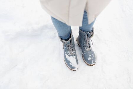 female feet in winter shoes on snow from top