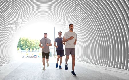 young men or male friends running outdoors Stok Fotoğraf