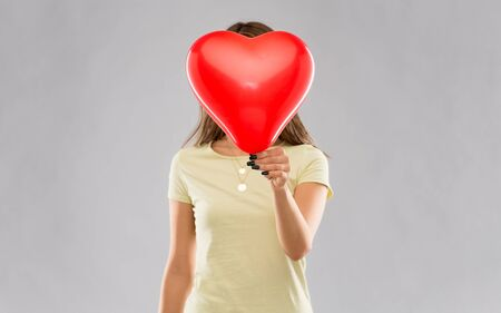 valentine's day and people concept - young woman covering face with heart-shaped balloon over grey background Stock fotó
