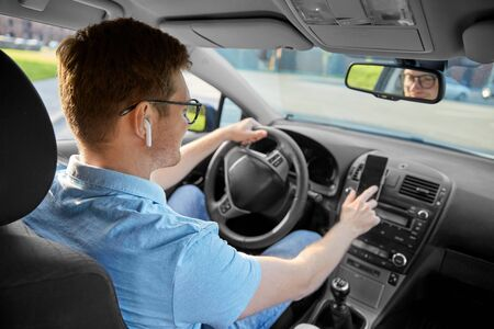 transport, vehicle and people concept - man or driver with wireless earphones driving car and using gps navigator on smartphone