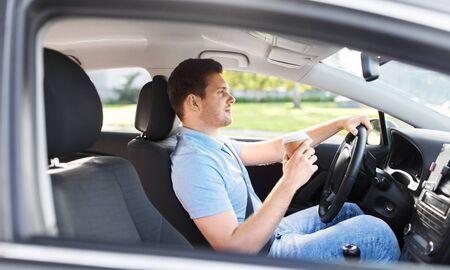 mężczyzna lub kierowca z filiżanką kawy na wynos jadący samochodem