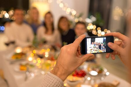 man taking picture of family at dinner party