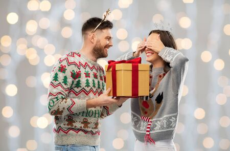happy couple in ugly sweaters with christmas gift Stock Photo