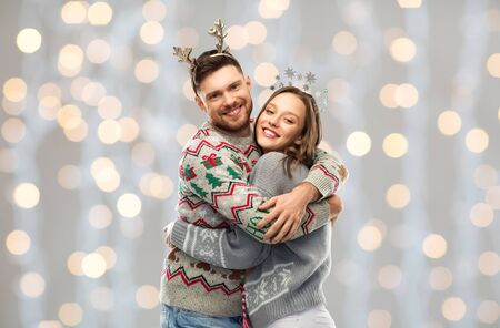 happy couple at christmas ugly sweater party Stock Photo