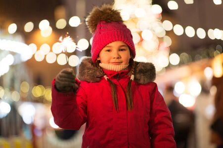 happy girl with sparkler at christmas market Standard-Bild - 131460518