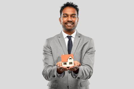 man realtor with house model and folder Banco de Imagens