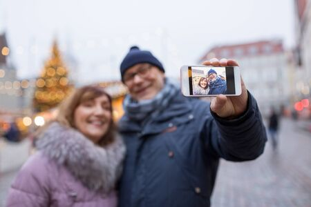 senior couple taking selfie at christmas market Standard-Bild - 131460864