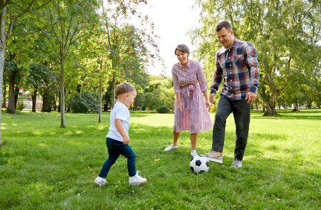 glückliche Familie, die Fußball im Sommerpark spielt