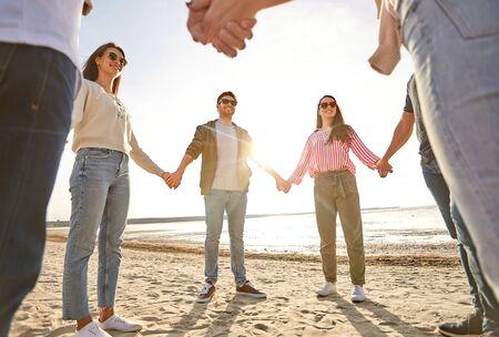 szczęśliwi przyjaciele trzymający się za ręce na letniej plaży