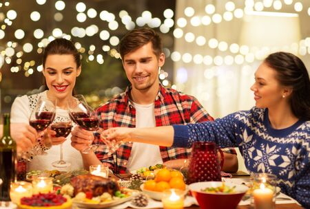 happy friends drinking red wine at christmas party Stockfoto