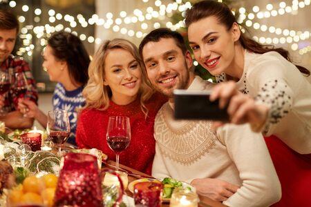 friends having christmas dinner and taking selfie Stockfoto