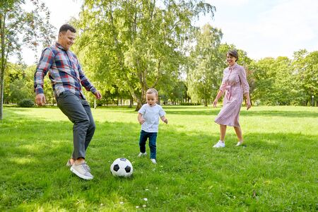 happy family playing soccer at summer park Stock Photo