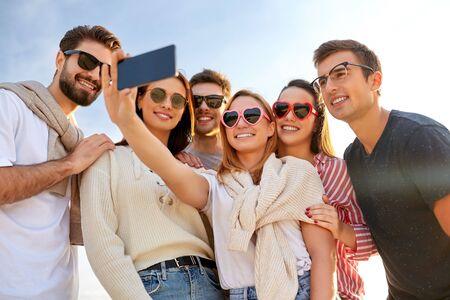 szczęśliwi przyjaciele robiący sobie selfie latem