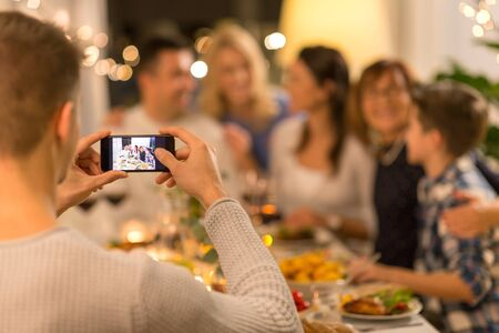 celebration, holidays and people concept - man with smartphone taking picture of family at dinner party Standard-Bild - 131358581