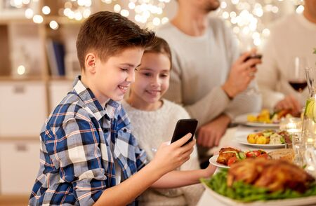 technology, holidays and people concept - happy boy with sister using smartphone having family dinner party at home