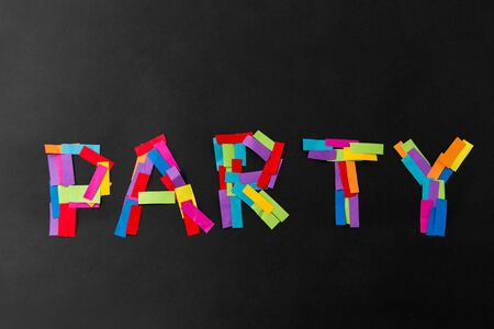 holidays, celebration and lettering concept - party word made of multicolored papers on black background