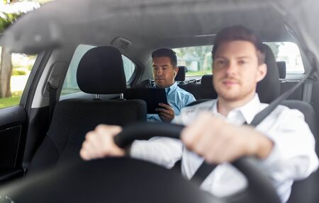 man with tablet pc and earphones riding in car
