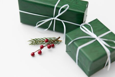 winter holidays, new year and christmas concept - gift boxes wrapped into green paper and fir tree branch with red berries on white background 版權商用圖片