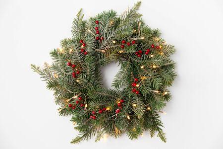 Vacaciones de invierno, año nuevo y concepto de decoración - corona de ramas de abeto con frutos rojos y guirnaldas de luces sobre fondo blanco.