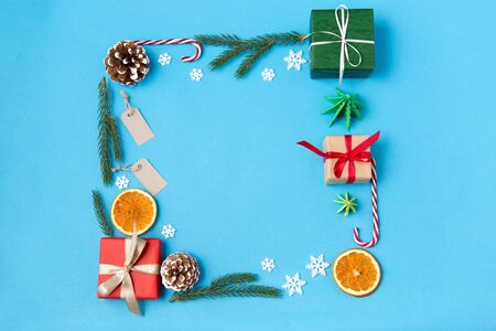 winter holidays, new year and christmas concept - frame made of gift boxes, fir tree branches, tags and decorations on blue background