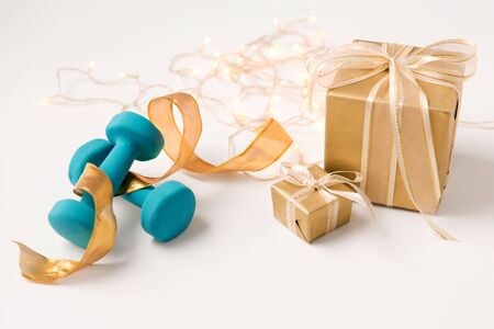 winter holidays, new year and christmas concept - gift boxes wrapped into golden paper and blue dumbbells on white background