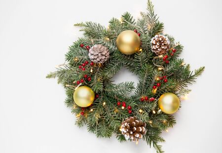 winter holidays, new year and decorations concept - wreath of fir branches with golden balls, pine cones and garland lights on white background