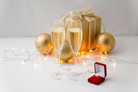 christmas, holidays and celebration concept - glasses of champagne and diamond ring in little red gift box