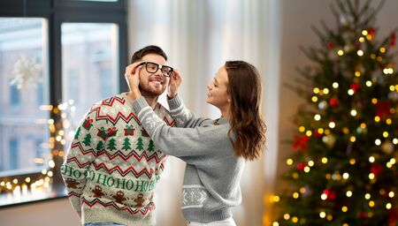 happy couple in ugly sweaters at home on christmas
