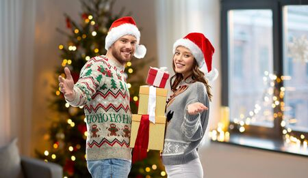 happy couple in christmas sweaters with gifts