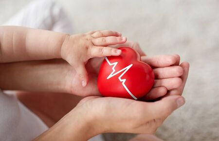 family, charity and health concept - close up of little baby and mothers hands holding red heart with ecg line